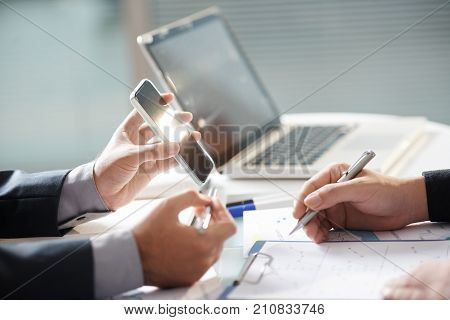 Close-up image of business executive showing application on smartphone screen to colleague