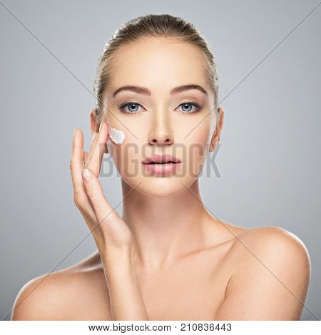 Beautiful young woman gets cream in the face. Skin care concept. Stunning caucasian woman with perfect health clean skin. Portrait of an Attractive girl  with blue eyes, closeup.  poster