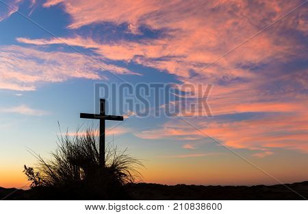 Black cross on a grass top sand hill at sunset.