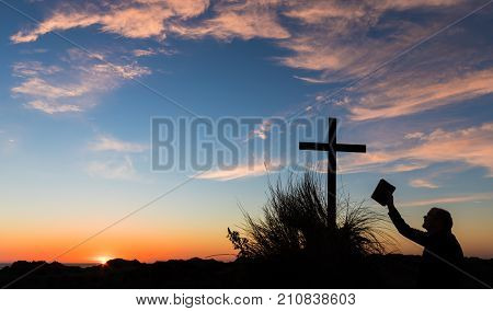 Man holding up The Bible to a cross on a sand hill with a wonderful sunset sky.
