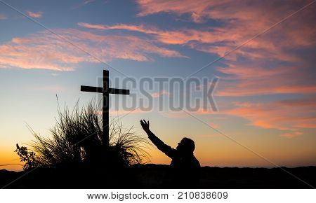 Man reaching his hand up to a cross at sunset.