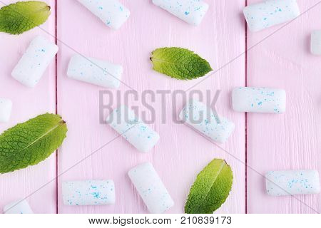 Chewing Gums With Mint Leafs On Pink Wooden Table