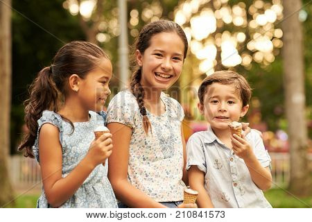 Happy Indonesian kids eating ice-cream and looking at camera