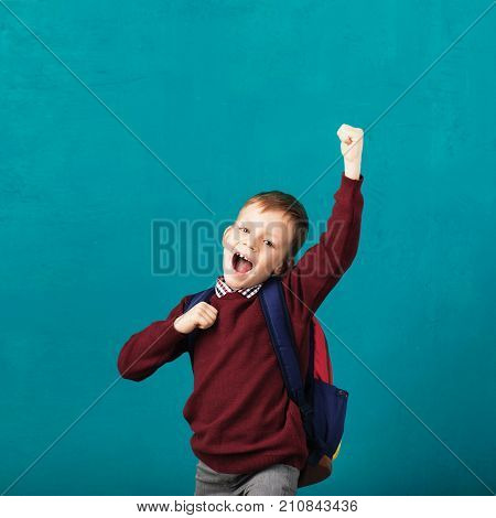Cheerful Smiling Little Boy With Big Backpack Jumping And Having Fun Against Blue Wall.