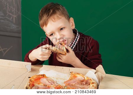 Kid Eating Pizza Slice From The Box At Fast Food Restaurant.