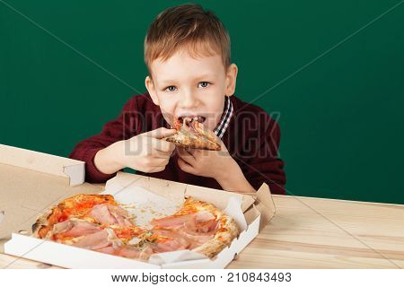 Child Eating Pizza Slice From The Box Close Up Photo