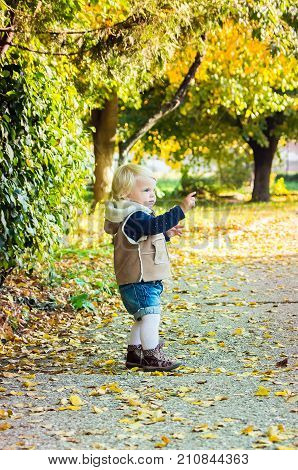 Happy Blond Girl Walking In The Autumn Park