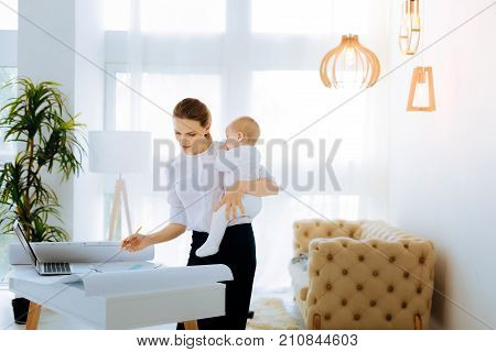 Only concentration. Thoughtful attentive responsible woman looking at the graphic while staying at home with her baby