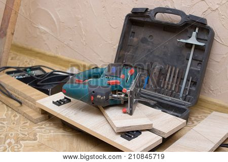 Lying on the floor is a joiner tool electric jig saw after cutting