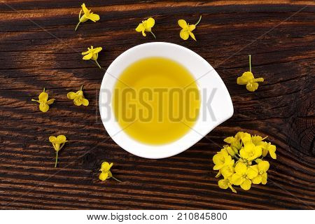 Rapeseed oil in white bowl on wooden table from above. Rape oil blossom. Oilseed rape. Folwers and oil.