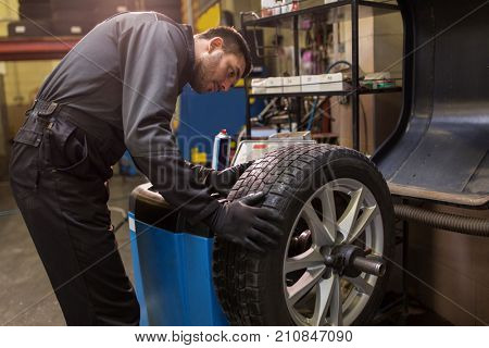 car service, repair, maintenance and people concept - auto mechanic man balancing tire at workshop