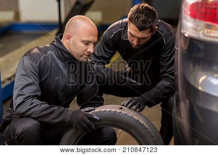car service, repair, maintenance and people concept - two auto mechanics changing car tires at workshop