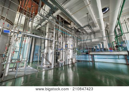 The rectification shop. Silvery distillation columns entangled in a multitude of pipes, valves and sensors.