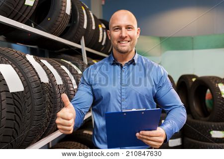 business, maintenance and people concept - male manager with wheel tires and clipboard showing thumbs up at car repair service or auto store