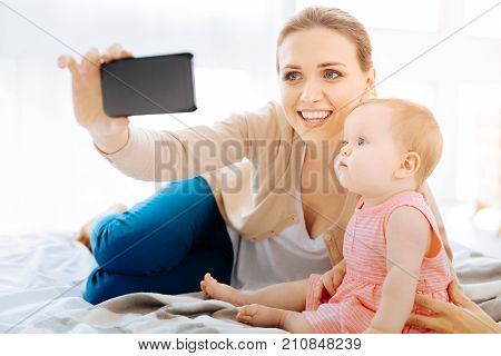 Taking photos. Cheerful happy excited woman taking photos with her calm little child