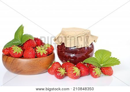 Strawberry jam. Strawberry jam in a transparent glass jar with a paper lid and fresh ripe strawberries in a round wooden cup on a white background.Strawberry season