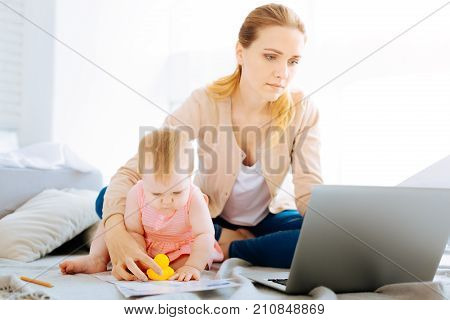 Difficult work. Tired young woman looking attentively at the screen of her laptop while a pretty child sitting by her side