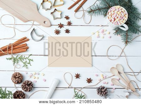 Top view compositions of food ingredients Marshmallow Mug Chopping board Cookie forms Pounder Anise stars Spoons on white wooden desk with empty card in center for your text Flat lay. Food Holiday