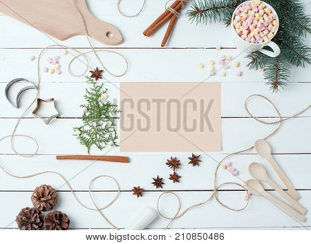 Top view compositions of food ingredients Marshmallow Mug cacao Cookie forms Pounder Anise stars Spoons on white wooden desk with empty card in center for your text Flat lay. Food Holiday cooking