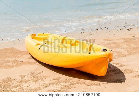 close-up of a yellow kayak at the water's edge on the sandy beach of Thailand