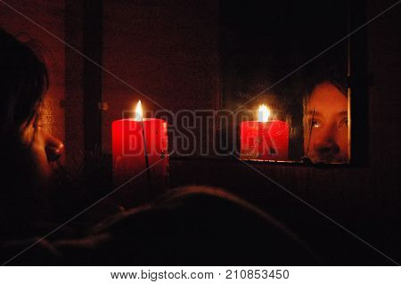 Christmas Fortune Telling. A Girl Looks At Her Reflection In A Mirror By Candlelight.