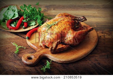 Whole roasted chicken on cutting board. Wooden rustic background .