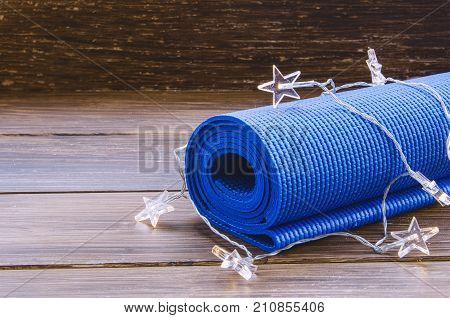 Blue exercise mat with Christmas garland on wooden background. Training on Christmas Day concept. Sport xmas concept. Copy space.