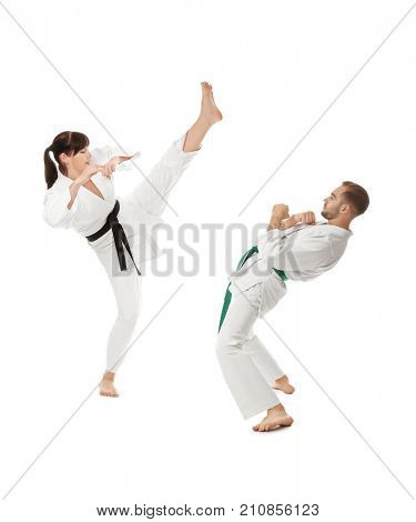 Young man and woman practicing karate on white background