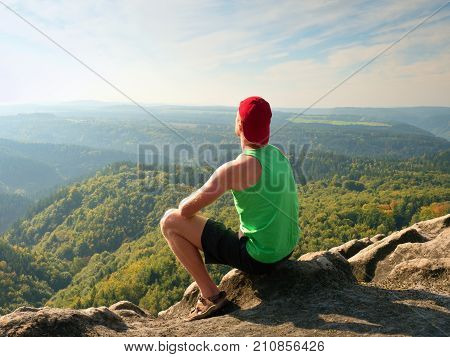 Tourist In Green Singlet And Black Shorts On Rock, Enjoy Nature Scenery. Valley In Sun Bath