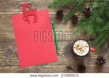 Christmas composition with red cup and empty red blank letter for Santa or your wishlist or advent activities invitation. Top view and space for your text.