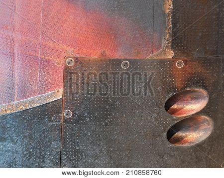 rusted burned steel red and black metal panels on a used soyuz entry landing capsule