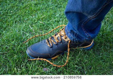 man sneakers unleashed lacing on the grass