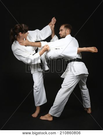 Young man and woman practicing karate on dark background