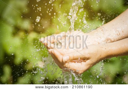 Woman washing hand outdoors. Natural drinking water in the palm. Young hands with water splash selective focus. Instagram