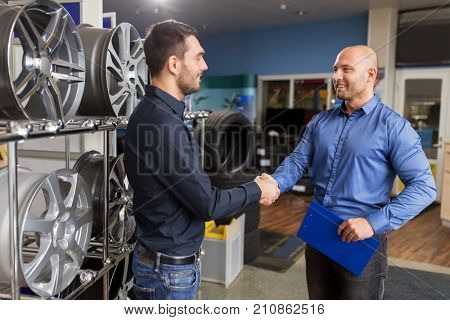 business, partnership and people concept - male customer and salesman shaking hands at car repair service or auto store