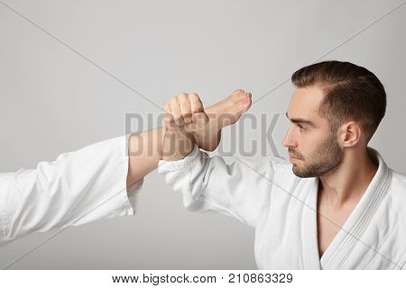 Young man in karategi blocking kick on light background