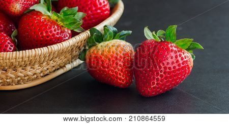 Goodness ripe strawberries on granite table with copy space use for web banner or cover and other web design.Red freshness strawberry on black isolated background in low key or still life concept. Fresh strawberry background for web design.