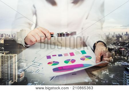 Businesswoman looking through a magnifying on table