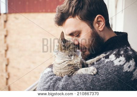 Cat and man portrait of happy cat with close eyes and young man people playing with the kitten. Handsome Young Animal-Lover Man Hugging and Cuddling his Gray Domestic Cat Pet