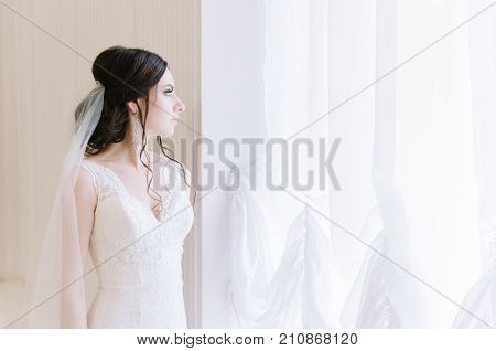 Beautiful Bride Perfect Style. Wedding Hairstyle Make-up Dress And Bride's Bouquet. Young Attractive