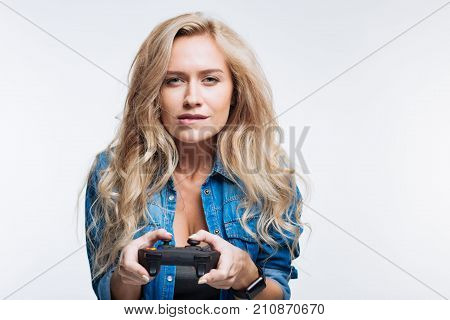 Adore playing games. Charming fair-haired young woman playing video games with a game controller while biting her lip