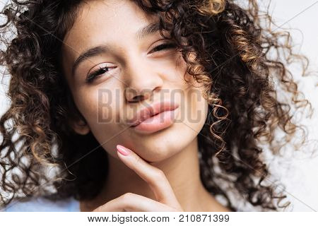Sensual attractiveness. Charming curly-haired dark-haired woman touching her chin with her finger and pouting while looking at the camera