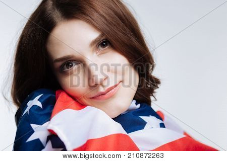 Proud American. The close up of a beautiful auburn-haired young woman leaning her cheek on the American flag, being wrapped into it
