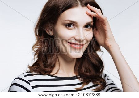 Cute smile. The close up of a charming auburn-haired young woman in a striped pullover pressing her hand to her temple and smiling at the camera while posing