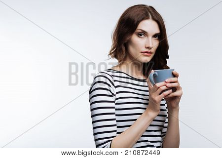 After sleepless night. Pretty auburn-haired young woman holding a cup of coffee, drinking it to fight lack of sleep