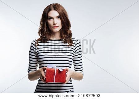 Gift for you. Pretty auburn-haired young woman in a striped pullover holding a beautifully wrapped gift box while posing against a white background