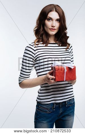 Happy holiday. Charming auburn-haired young woman in a striped pullover holding a red gift box tied up with a bow while posing against a white background poster