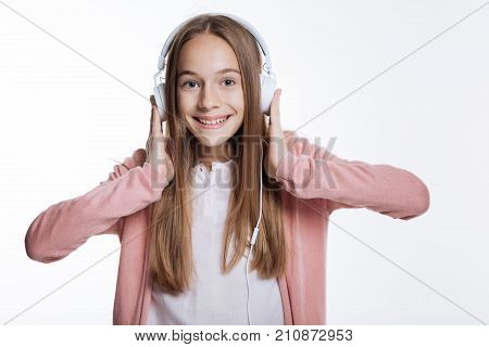 Mood-improving music. Adorable teenage girl listening to the music in headphones and pressing them closer to her ears while smiling broadly