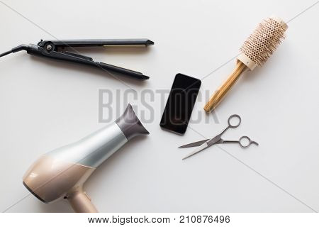 hair tools, beauty and hairdressing concept - smartphone, scissors, hairdryer with hot styling iron and curling brush on white background