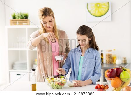 food, healthy eating, family and people concept - happy mother and daughter cooking and salting vegetable salad for dinner at home kitchen